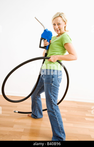 Portrait of adult blonde woman holding gas nozzle like a gunslinger - Stock Image