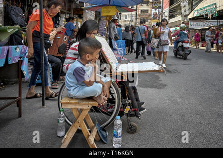 Disabled woman in a wheelchair. Young female selling lottery tickets accompanied by her young brother. Thailand street scene, Southeast Asia - Stock Image