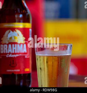 Petropolis, Rio de Janeiro, Brazil- December 21, 2018: A bottle of Brahma beer in a bar setting beside a full cup, side view, crop - Stock Image