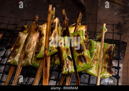 Cambodia, Phnom Penh, Oudong, food market, barbecuing parcels of sticky rice wrapped in pandanus leaved - Stock Image