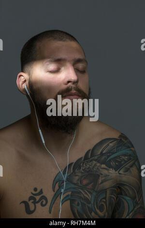 Serene bare chested man with beard and tattoos listening to music with earbuds - Stock Image