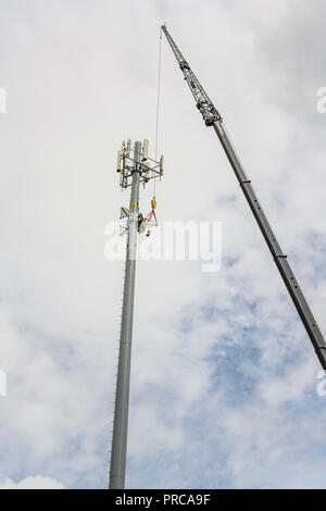 Cell tower repair or new installation of 5G telecommunications network using a tall crane in Montgomery Alabama, USA. - Stock Image