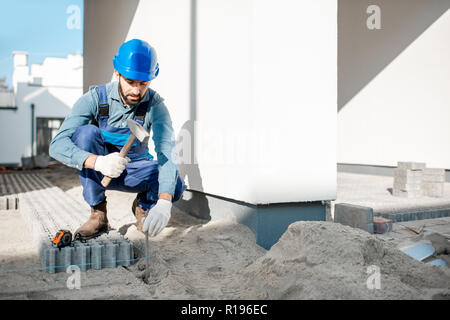 Builder in uniform mounting paving tiles hammering a pile on the construction site outdoors - Stock Image