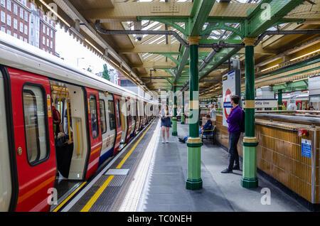 A train waits at the platform at South Kensington London Underground Station. - Stock Image
