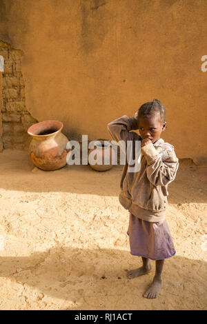 Samba village, Yako Province, Burkina Faso : a young girl, watches while her mother talking to other villagers. - Stock Image