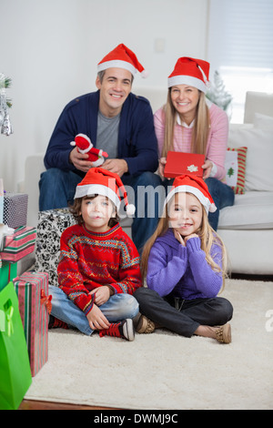 Family In Santa Hats At Home During Christmas - Stock Image
