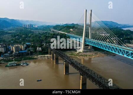 (190423) -- CHONGQING, April 23, 2019 (Xinhua) -- Aerial photo taken on April 23, 2019 shows the previous (L) and the new Baishatuo Yangtze River railway bridge in Jiangjin of southwest China's Chongqing Municipality. The previous Baishatuo Yangtze River railway bridge, completed in 1959, will stop service after April 24. All trains will run on the new double decker steel truss cable stay railway bridge after that day. The new bridge has 4 tracks on the upper deck for passenger trains with a designed speed of 200 kilometers per hour and 2 tracks on the lower deck for cargo trains with the desi - Stock Image