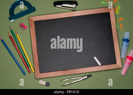 School concept. Empty chalk board, stationery on green background, blank copy space. - Stock Image