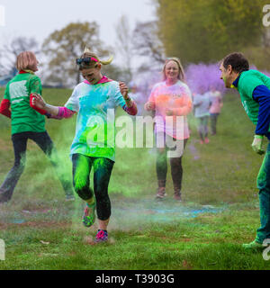 Young woman runner being covered in paint on Macmillan cancer charity 5K color fun run. - Stock Image