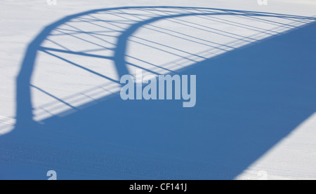 Shadow image of a bridge on snow surface - Stock Image