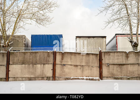 Trucks standing behind the fence wall in winter - Stock Image