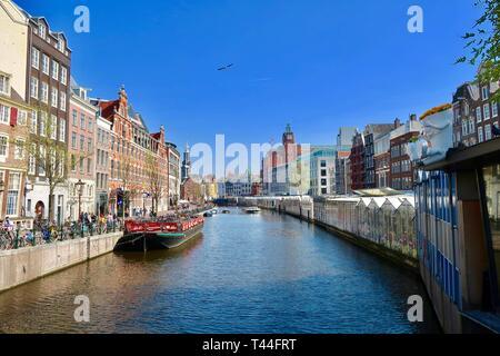 Amsterdam, Netherlands - April 2019: Floating flower market and floating bike park on the Singel canal. - Stock Image