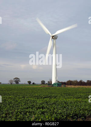 Onshore wind turbines on farmland at Somerton near the Norfolk coast spinning in a light autumn breeze. - Stock Image