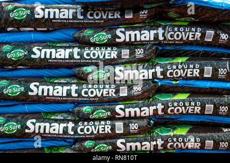 A stack of bags of Smart Ground Cover decorative mulch in a garden centre - Stock Image
