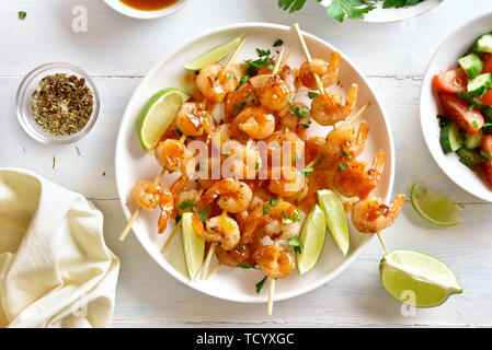 Delicious prawns skewers with greens, spices, lime and sauce on white plate over wooden table. Grilled shrimp skewers. Tasty seafood. Top view, flat l - Stock Image