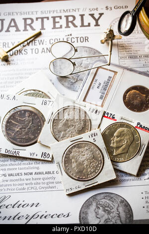 Numismatic Coin Collector - Trade Dollar - Morgan Dollars - Ike Dollar - Kenney Half on a back droop of Quarterly Grey Sheet - Stock Image