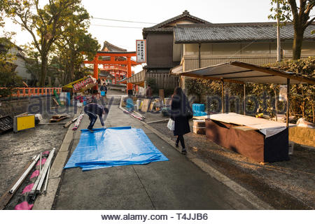 Vendors setting up food stalls along lane in the early morning before the crowds of tourist pass by on their way to the Fushimi Inari Taisha shrine, F - Stock Image