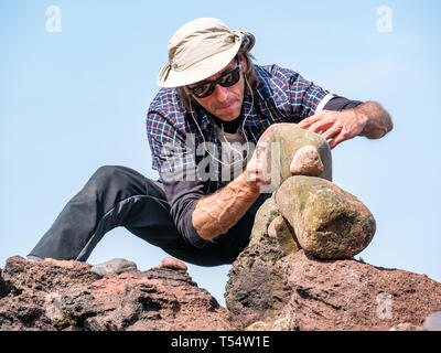 Dunbar, East Lothian, Scotland, UK. 21st Apr 2019. European stone stacking championship: Pedro Duran, from Spain and overall winner of last year's competition  balances stones in the artistic competition, giving competitors 3 hours to create anything from stones or found objects  competition at Eye Cave beach on the second day which comprises 2 competitions, a 3 hour artistic challenge and a children's competition. The overall winner receives a trip to llano Earth Art Festival & World Stone Balancing competition in Texas in 2020. Credit: Sally Anderson/Alamy Live News - Stock Image