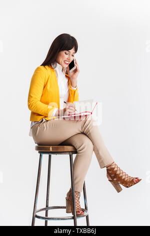 Image of a beautiful young business woman posing isolated over white background talking by mobile phone writing notes. - Stock Image