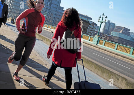 A young woman running in lycra over Southwark Bridge and a person with luggage walking on a sunny day in winter London England UK  KATHY DEWITT - Stock Image