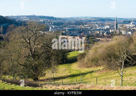 View across an ancient meadow with sheep grazing looking over the historic English city of Bath and hills beyond - Stock Image