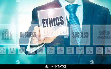 Businessman pressing an Ethics concept button. - Stock Image