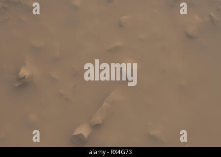 Close up of dirty muddy puddle gravel road after rain. - Stock Image