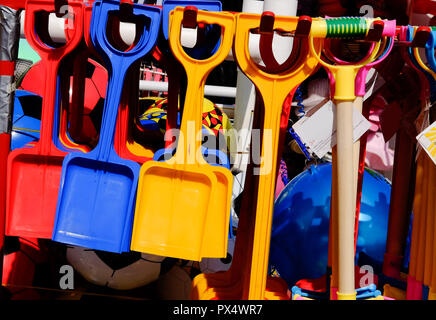 Multicoloured toys and beach spades for sale at beachfront kiosk - Stock Image