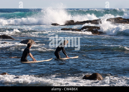 Two surfers going into the surf at Moses Rock beach, Western Australia - Stock Image