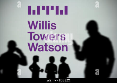 The Willis Towers Watson logo is seen on an LED screen in the background while a silhouetted person uses a smartphone (Editorial use only) - Stock Image