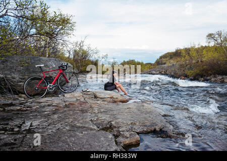 Cyclist sitting at river - Stock Image