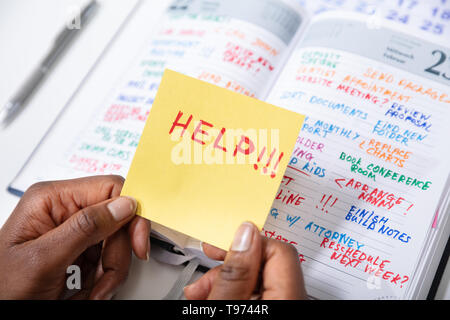 Close-up Of Person's Hand Holding Adhesive Note With Help Text Over Diary - Stock Image