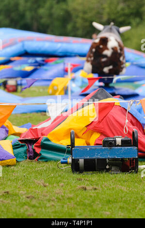 Bouncy castles laid out and ready to be inflated - Stock Image
