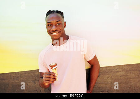Young handsome black man wears a pink t-shirt, smiles and holds a ice cream cone in summertime on a painted wall as a sunrise or sunny day - Stock Image