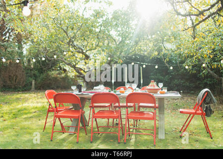 Garden party table and string lights in sunny backyard - Stock Image