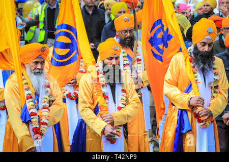 Gravesend, Kent, UK, 13th April 2019. The guards at the front of the procession, followed by the float containing the shrine. Sikh participants wear the traditional kirpan, a dagger or sword, and turban. Thousands of spectators and religious visitors line the streets of Gravesend in Kent to watch and participate in the annual Vaisakhi procession. Vaisakhi is celebrated by the Sikh community all over the world. - Stock Image