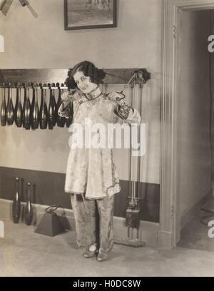 Woman in silk pajamas exercising in gym - Stock Image