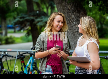 Two female university students standing and talking together beside a bike rack on campus; Edmonton, Alberta, Canada - Stock Image