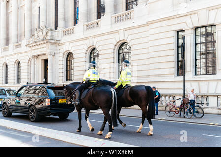 London, UK - May 15, 2019: English Police officers mounted on horseback patrolling near Whitehall in Westminster - Stock Image