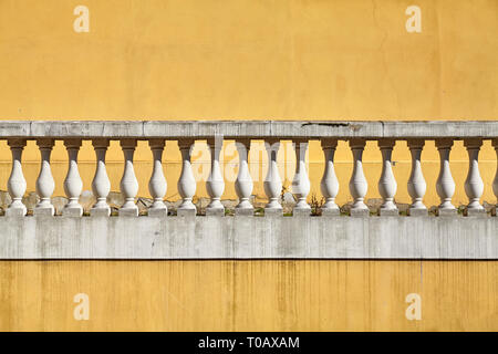 Old balustrade against yellow wall, architectural background. - Stock Image