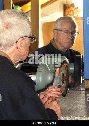 A man in his sixties sharpening a chisel using a bench grinder in a home workshop. - Stock Image