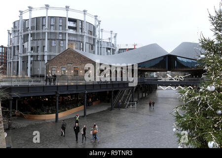 People and Christmas tree in Coal Drops Yard and view of Gasholders apartments at Kings Cross area in London N1C England UK  KATHY DEWITT - Stock Image