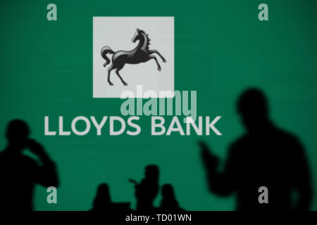 The Lloyds Bank logo is seen on an LED screen in the background while a silhouetted person uses a smartphone in the foreground (Editorial use only) - Stock Image