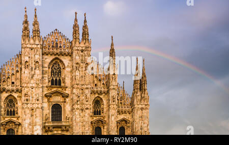 Facade of Milan, Italy's Duomo cathedral with a beautiful rainbow on background. - Stock Image