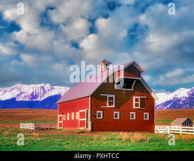 Barn with white trim and pasture with Wallowa Mountains. Oregon - Stock Image