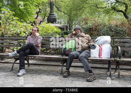 Two men on a bench with their hand resting on their cheek. In Union Square Park in Manhattan, NYC. - Stock Image
