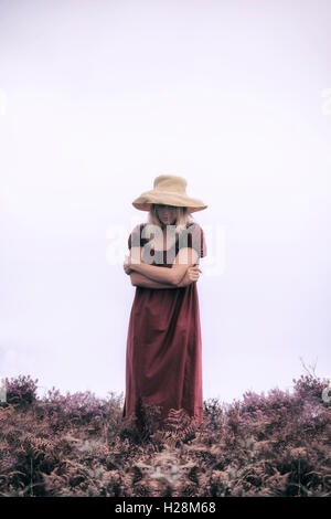 a woman in a red dress is standing in the heather - Stock Image