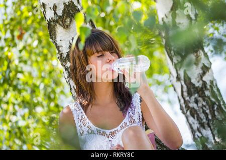 Attractive teenager girl is drinking fresh water from bottle in nature - Stock Image