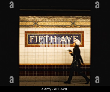 Woman walking past Fifth Avenue subway sign, New York City, going shopping - Stock Image