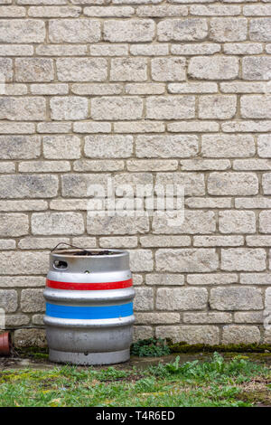 Single metal beer barrel keg with red, white, and blue stripes, stood against a wall of sandy stone bricks and a strip of grass in the foreground. - Stock Image